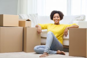Black woman smiling with moving boxes
